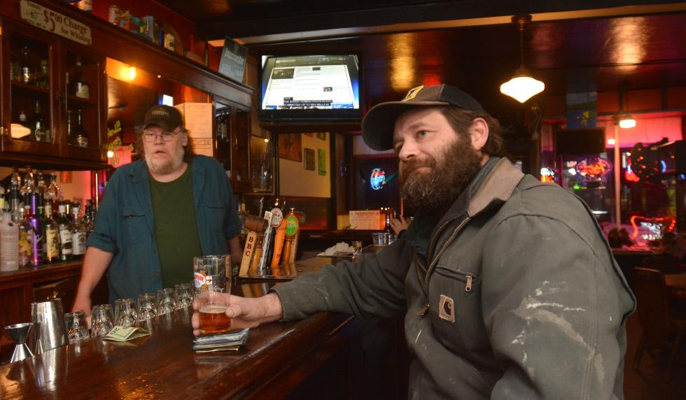 JERREY ROBERTS Paul Ayotte, right, of Northampton, has a beer while watching TV at Hugo's in Northampton. Chris Wenz, the bar's manager, tends the bar. - JERREY ROBERTS | DAILY HAMPSHIRE GAZETTE