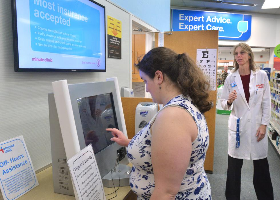 JERREY ROBERTS Stacie Manning, left, of Holyoke, uses a kiosk to check in at the CVS Minute Clinic Wednesday on King Street in Northampton. Connie Turner, who is a nurse practitioner, looks on. - JERREY ROBERTS | DAILY HAMPSHIRE GAZETTE