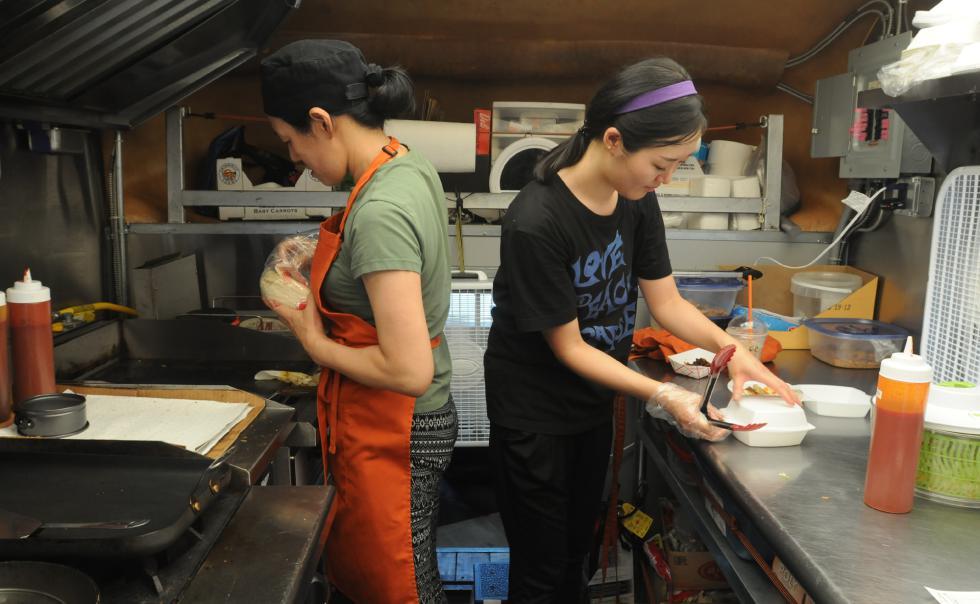 CAROL LOLLIS  left, Cecilia Park with Jane Kim making food in Sun Kim's food truck in Springfield. - Carol Lollis | Daily Hampshire Gazette