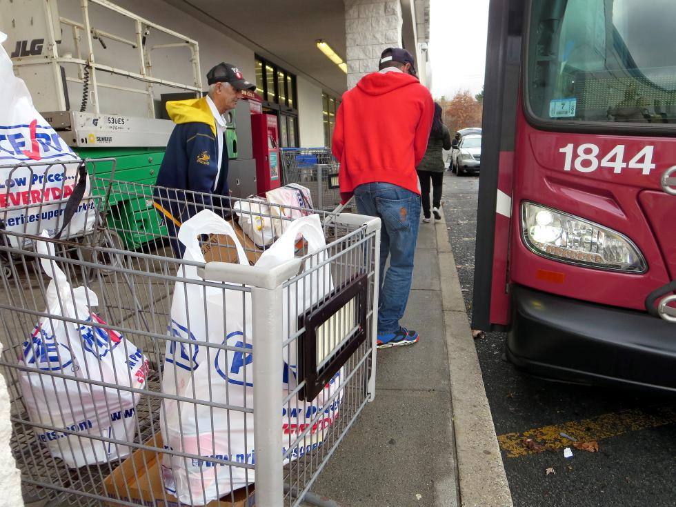 KEVIN GUTTING Osvaldo Morales, left, 68 of Chestnut Street in Springfield helps friend Julio Sanchez, 44, of Dwight Street to lift his hand cart onto an westbound PVPA B-7 bus after shopping at the Price Rite supermarket on Boston Road in Springfield on Friday. - KEVIN GUTTING | DAILY HAMPSHIRE GAZETTE