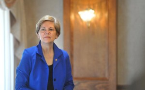 KEVIN GUTTING U.S. Senator Elizabeth Warren, D-Mass, listens to her introduction to speak to the 2014 Conference for Franklin and Hampshire County Municipal Officials at the Clarion Hotel and Conference Center in Northampton Saturday. - KEVIN GUTTING | Daily Hampshire Gazette
