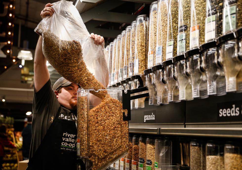 DAN LITTLE Grocery employee Taylor Roberts refills the bulk section Wednesday at River Valley Market Co-op in Northampton. - DAN LITTLE | DAN LITTLE