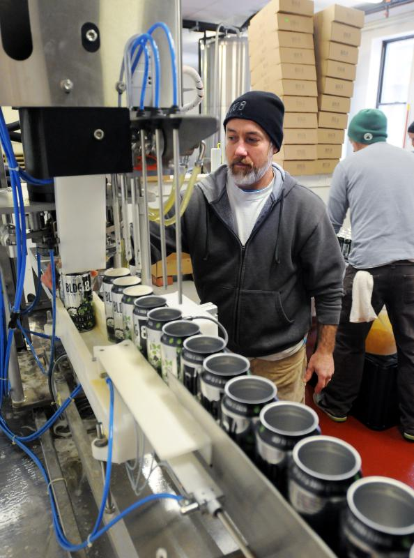 KEVIN GUTTING Brewer Mike Yates works the canning line at Building 8 Brewing in Florence. - KEVIN GUTTING | DAILY HAMPSHIRE GAZETTE