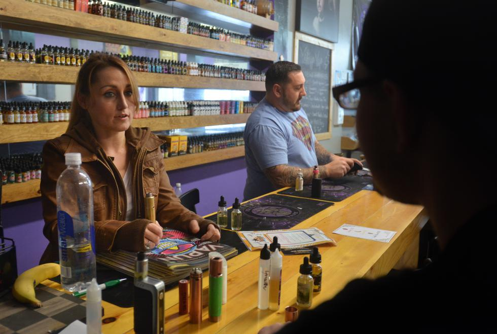 Meagan Leckie and Nick Friscia talk to customers at Voltage Vape in Sprinfield, Tuesday, March 8. Leckie is the manager of the Enfield store; Friscia is a co-owner. - JERREY ROBERTS | DAILY HAMPSHIRE GAZETTE