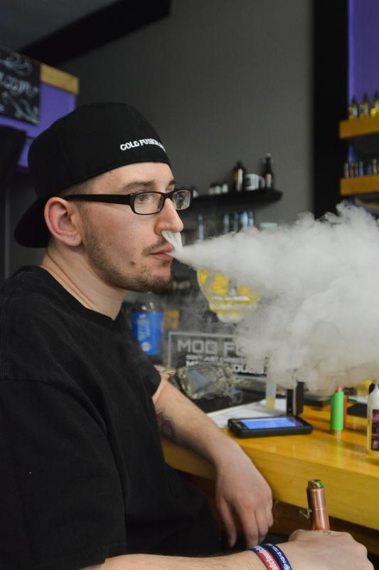 Chris Ballard, of Springfield, exhales vapor at Voltage Vape in Springfield, Tuesday, March 8. - JERREY ROBERTS | DAILY HAMPSHIRE GAZETTE