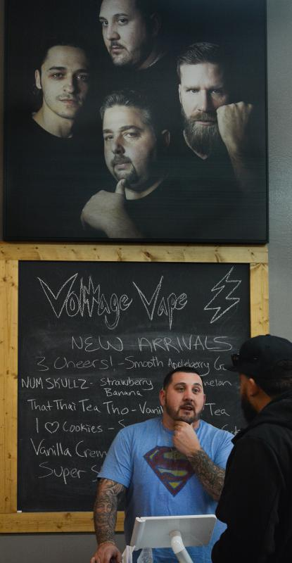 Nick Friscia, who is a co-owner of Voltage Vape, talks to a customer at the company's Springfield location, Tuesday, March 8. Hanging overhead is a portrait of him with the company's co-owners and a former employee, left. - JERREY ROBERTS | DAILY HAMPSHIRE GAZETTE