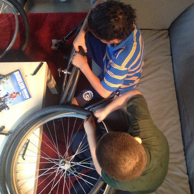 Kids change a tire at a bicycle repair clinic at the makerspace.