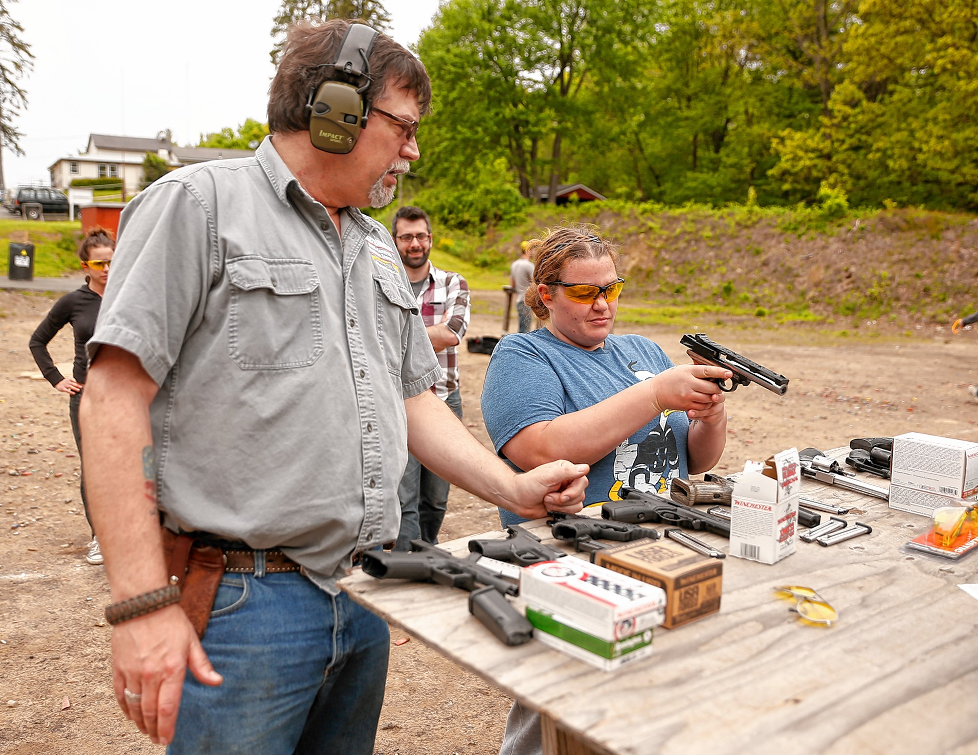 Instructor Kirk Whatley, left, helps Rebecca Stupski, of Hardwick, select a pistol to practice firing during a group firearms training class Saturday at Norwottuck Fish and Game in Amherst.