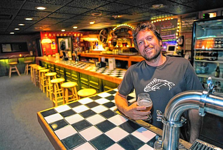 Wendell Rheinheimer, co-owner of the Root Cellar in Greenfield, with a special house beer by Stoneman Brewing. Photo: Paul Franz for the Recorder.