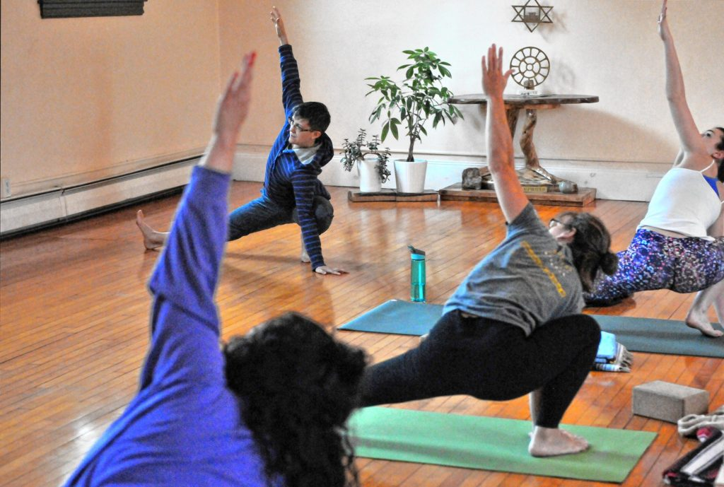 —GAZETTE STAFF / KEVIN GUTTINGJacoby Ballard leads an early morning class Friday at Yoga Center Amherst.