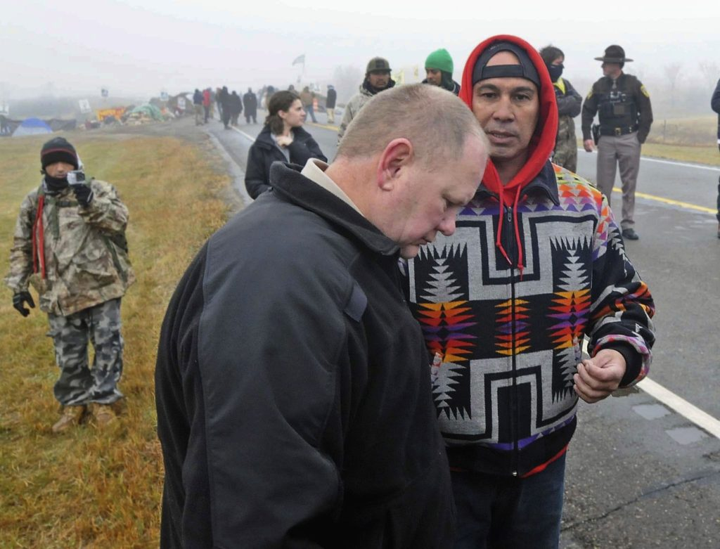 FILE - In this Oct. 26, 2016 file photo, Morton County Sheriff Kyle Kirchmeier, front, listens to Brian Wesley Horinek, of Oklahoma, outside the New Camp on Pipeline Easement in North Dakota. Kirchmeier, who has led the police response to the Dakota Access oil pipeline, is a law enforcement lifer, a veteran of the North Dakota State Patrol and National Guard before being elected to his first term as Morton County sheriff. (Tom Stromme/The Bismarck Tribune via AP, File) /The Bismarck Tribune via AP)