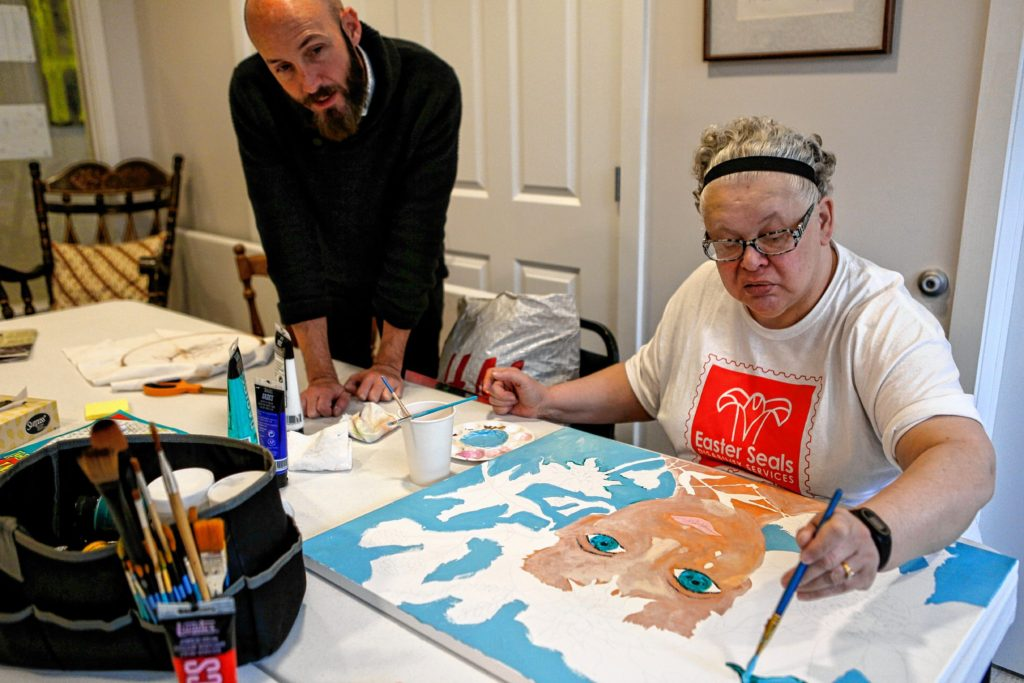 LouAnn Hazelwood, who lives in Soldier On's transitional housing for female veterans on the Veterans Affairs campus in Leeds, right, works with the guidance of Arts Director Nathan Hanford to paint a piece Nov. 15, 2016 in memory of her late cousin who passed away from cancer in the 1970s. Hazelwood plans to donate the painting to Berkshire Medical Center's cancer center, upon completion.