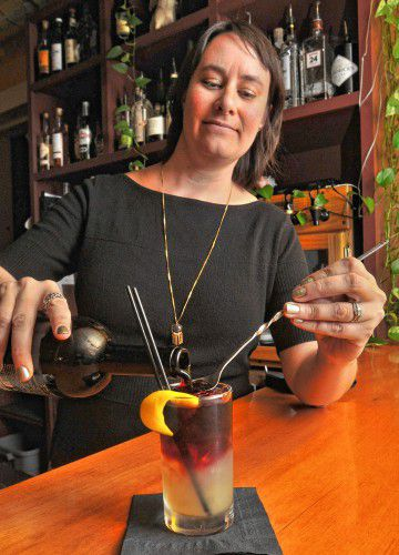 Elizabeth Martinez, who is the owner of Bistro Les Gras, pours red wine to finish a New York Sour.