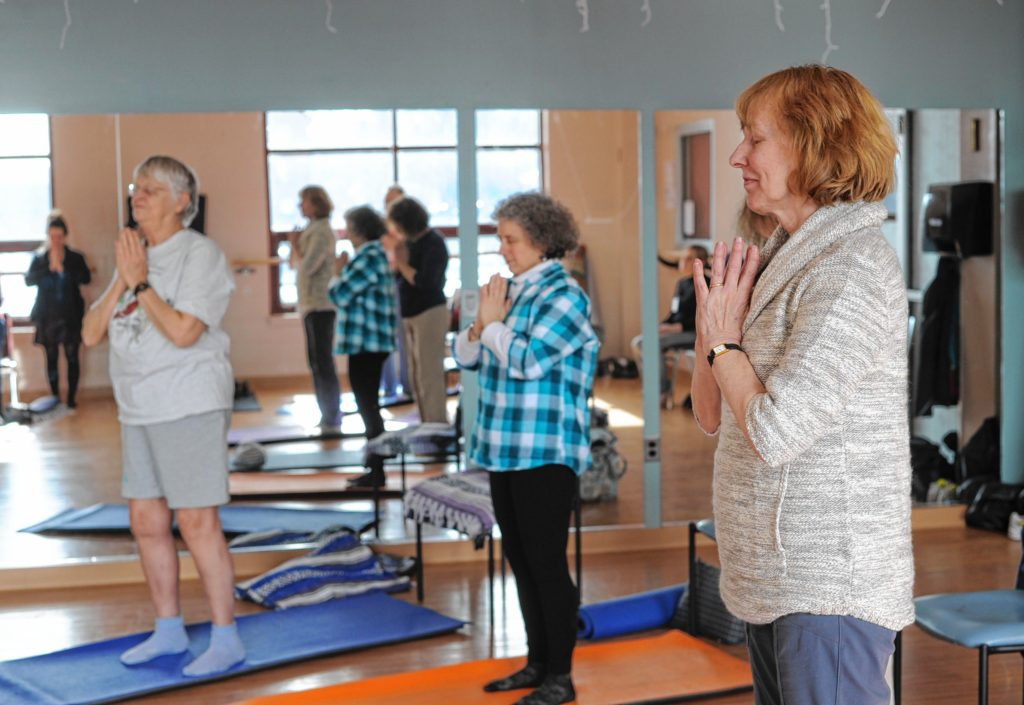 From left, Suzanne Carlson of Greenfield, Kim Audette of Sunderland and Karen Latka of Montague participate in a yoga class for people dealing with cancer at the Greenfield YMCA.   February 22, 2017.