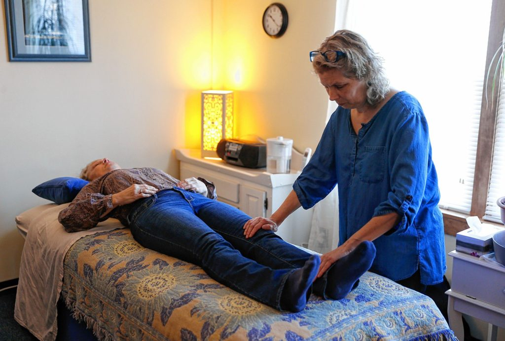 Volunteer Paula Barron, who is a specializes in lymphatic massage and cranial sacral therapy, works with a client Wednesday at the Lyme Disease Resource Center in Northampton.