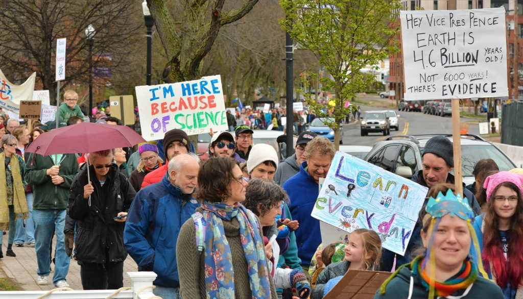 Hundreds of people walk in the March for Science on North Pleasant Street in Amherst on Earth Day, Saturday.