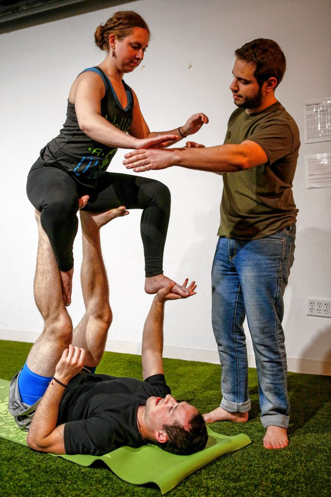 Etai Dvora of Northampton, right, spots as Hampshire College student Elizabeth Levick, top, and Jason Potash of Northampton transition from straddle throne to easy throne March 31, 2017 during an acroyoga meet up at Mill 180 Park in Easthampton.