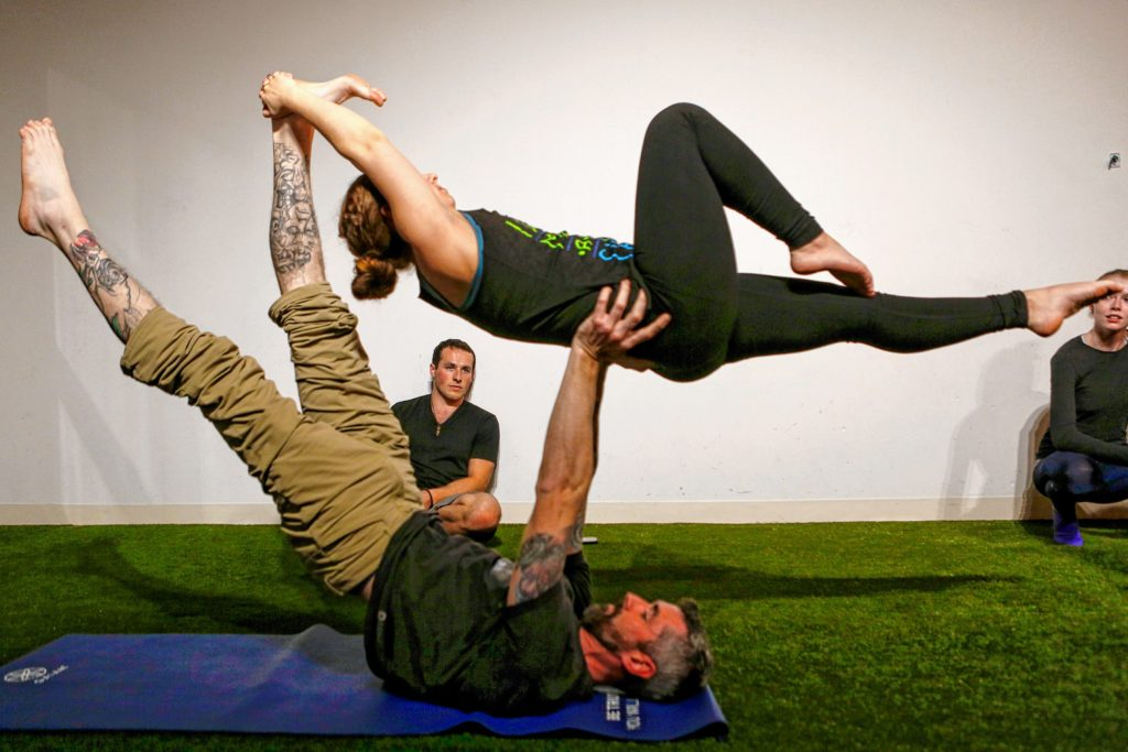 Jason Potash of Northampton, center, watches as Hampshire College student Elizabeth Levick and Brian Begley of Pittsfield perform a counterbalance March 31, 2017 during an acroyoga meet up at Mill 180 Park in Easthampton.