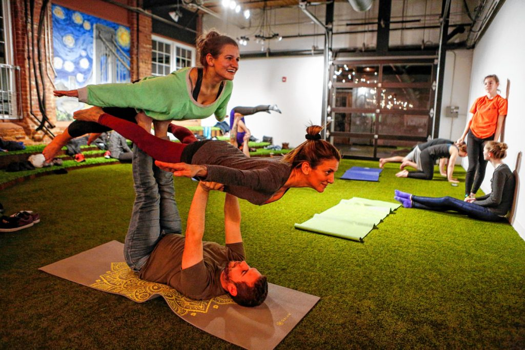 Etai Dvora of Northampton, bottom, holds up Dorin Ben-Ami of Northampton, center, and Gazette journalist Amanda Drane to perform double bird pose March 31, 2017 during an acroyoga meet up at Mill 180 Park in Easthampton.