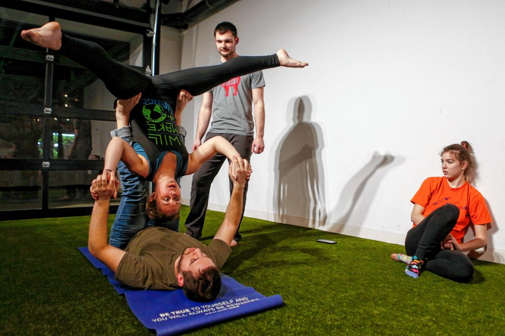Etai Dvora of Northampton, bottom, and Hampshire College student Elizabeth Levick pause in straddle bat pose while Will Witecki of Newington, Conn., and Hampshire College student Abbi Wilson look on March 31, 2017 during an acroyoga meet up at Mill 180 Park in Easthampton.