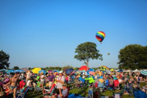 Hot air balloons lift off behind a field filled with attendees of the Green River Festival on the campus of Greenfield Community College, Saturday July 11. Recorder/Matt Burkhartt