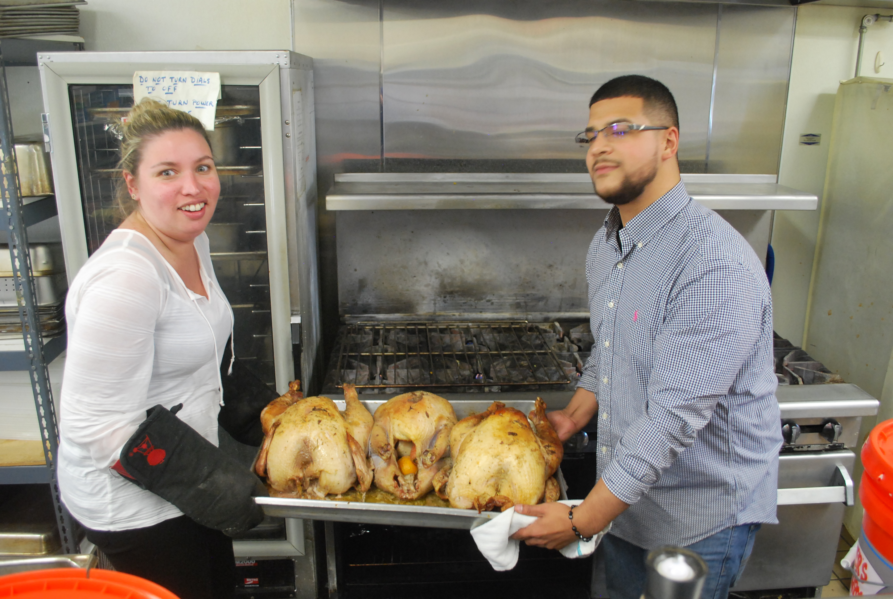 Andrea Marian (left) and Rube Reyes (right) pull turkeys out the oven for  the Nov. 27 community dinner at Lorraine's Soup Kitchen and Pantry in  Chicopee.