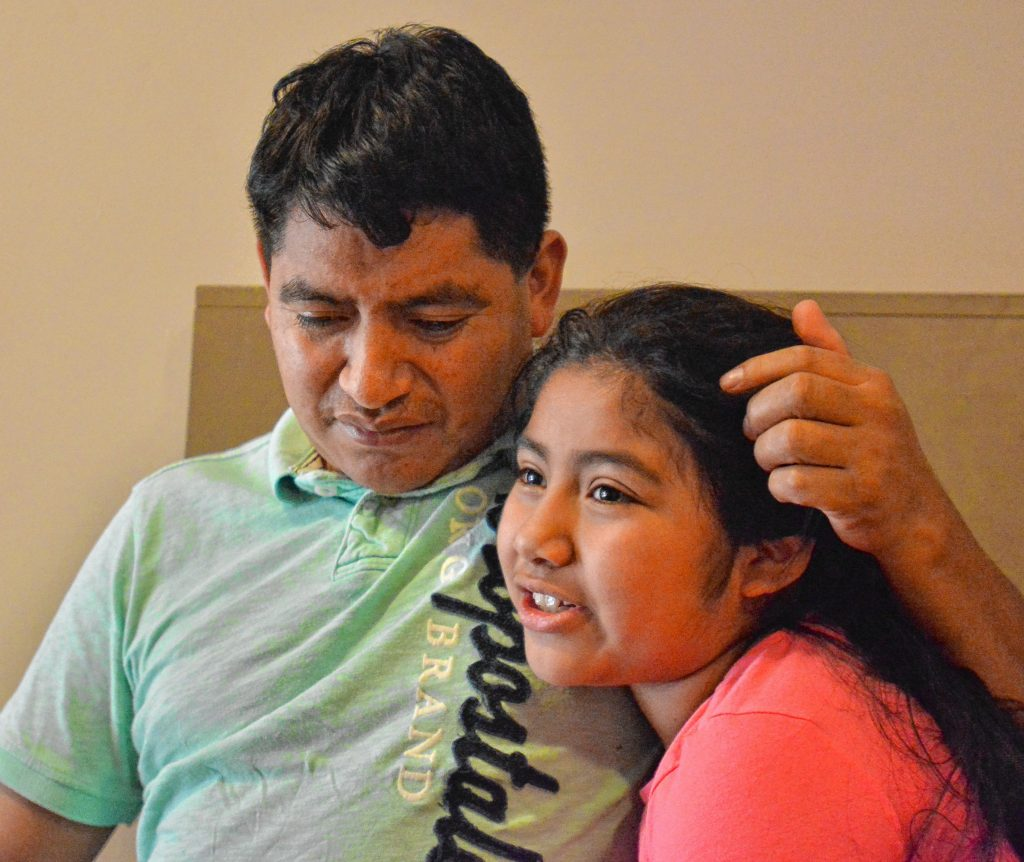 Lucio Perez, of Springfield, who is an undocumented immigrant who was facing deportation until he took refuge at First Congregational Church of Amherst Oct. 18, listens as his daughter, Lucy, 8, talks about how she misses seeing him, Saturday at the church.