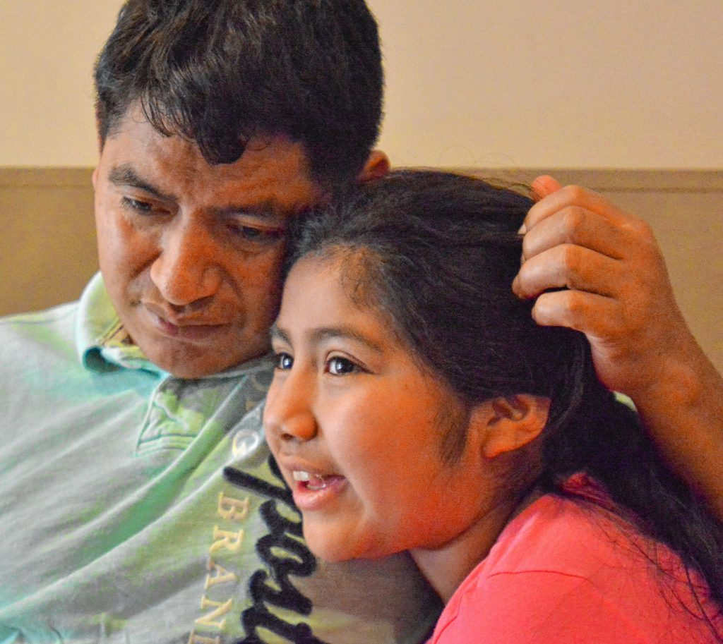 Lucio Perez, of Springfield, an undocumented immigrant  facing deportation, took refuge at First Congregational Church of Amherst Oct. 18. During an interview  Saturday at the church, Perez listens as his daughter, Lucy, 8, talks about how she misses seeing him.