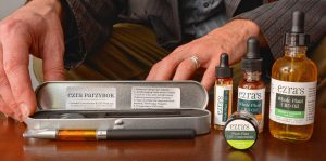 Ezra Parzybok displays his CBD products at his home office in Northampton.
