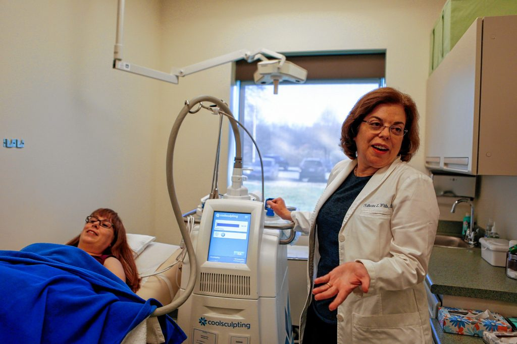 Dr. Katherine L. White describes how CoolSculpting works at her office at  Hampshire Dermatology in Northampton while  Carter, who works for her, receives the treatment.
