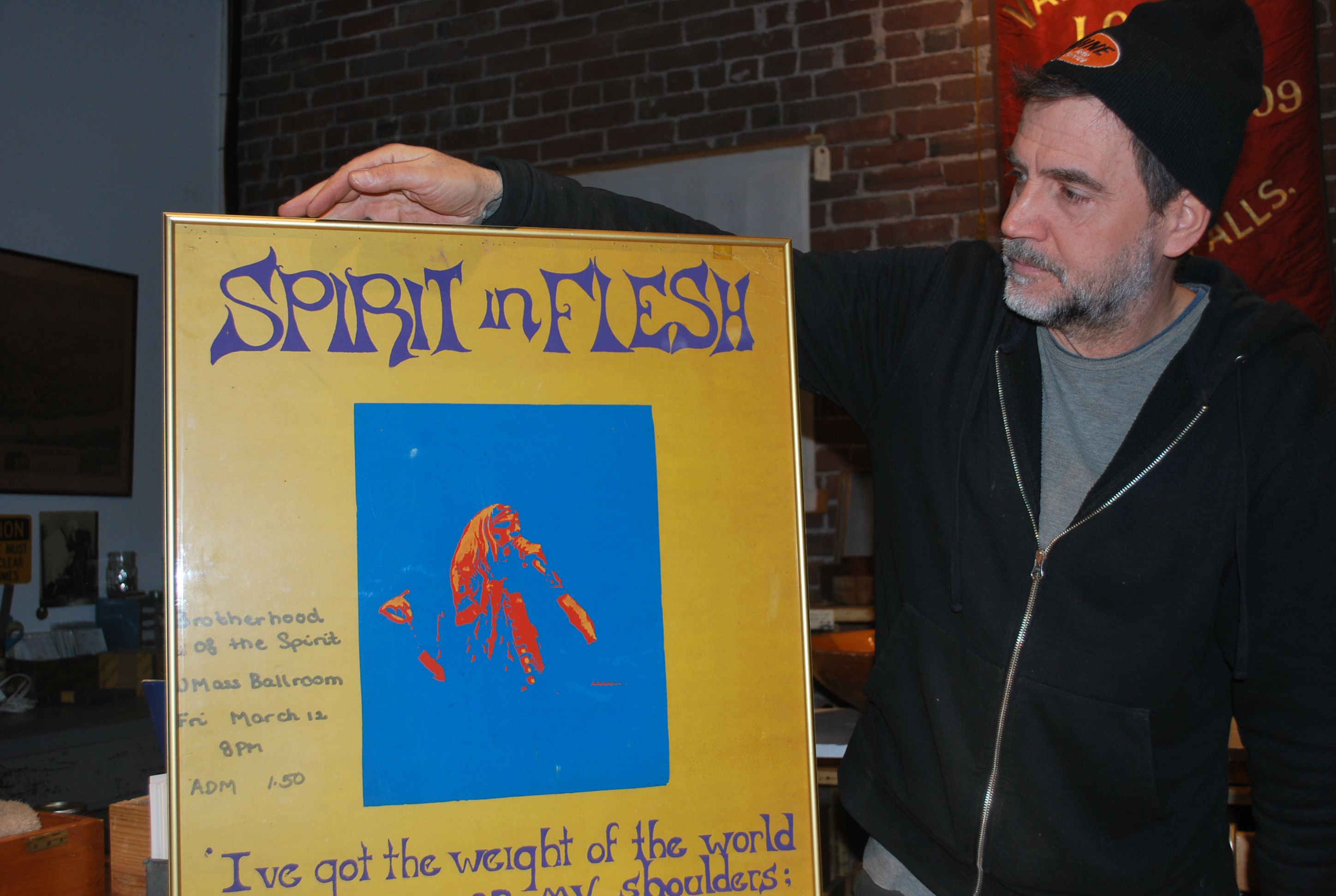 John McNamara, co-owner of Loot, holds up a poster for a Renaissance  Community organized show at UMass Amherst. The Renaissance Community was a  commune that ...