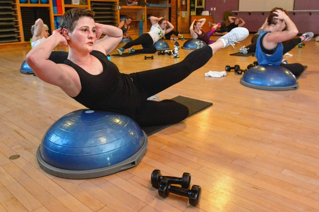 Christy Crutchfield, front, and others work their core muscles during Zawacki's high intensity interval training class  at Northampton Athletic Club.