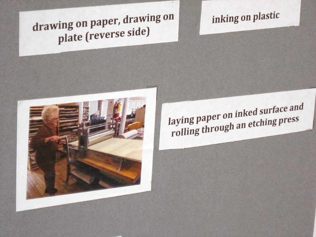 Doris Madsen is seen here laying paper on an inked surface and rolling through an etching process to create her artwork.