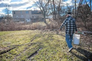 "John Coughlin uses what he calls his ""nipper nabber"" to pick up empty discarded 50 ml single-use plastic bottles of liquor not far from his home in Agawam on Wednesday, April 10, 2019."