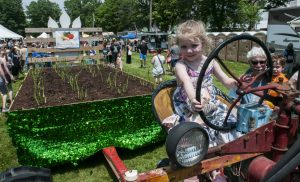 Fiona McNutt, 4, of Amherst takes a turn sitting in the driver's seat of a McCormick Farmall tractor that pulled the Boisvert Farm asparagus float to the WGBY Asparagus Festival on the Hadley Town Common on Saturday, June 2, 2018.