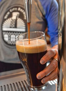 "Leah Jacobson pours a Lick the Spoon Chocolate Stout on nitro at New City Brewery in Easthampton, Tuesday, May 28, 2019. Katrina Pierson, the taproom manager said the combination, ""mellows the sour taste and adds ginger spice."""