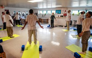 "Dori Digenti, center, begins a ""Seeds to Flowers"" yoga class with seven men enrolled in the Cultivating, Honoring and Awakening Men's Potential program, or CHAMP, at the Hampden County Pre-Release Center in Ludlow on Tuesday, April 30, 2019. Digenti is owner and founder of Breathing Space Yoga and Mindfulness Studio in Holyoke."