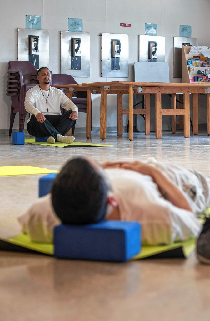 Steven, left, and Johnny, inmates at the Hampden County Pre-Release Center in Ludlow, assume a restorative pose at the end of a yoga class in the Cultivating, Honoring and Awakening Men's Potential program, or CHAMP, on Tuesday, April 30, 2019.