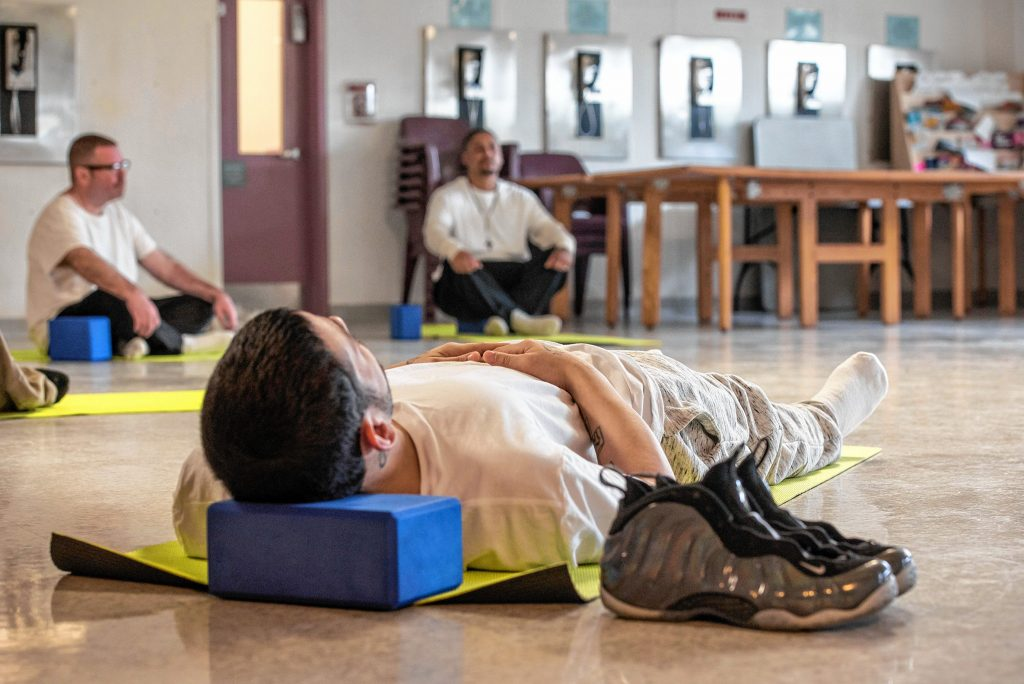Johnny, in foreground, Carlo, left, and Steven, inmates at the Hampden County Pre-Release Center in Ludlow, assume a restorative pose at the end of a yoga class in the Cultivating, Honoring and Awakening Men's Potential program, or CHAMP, on Tuesday, April 30, 2019.