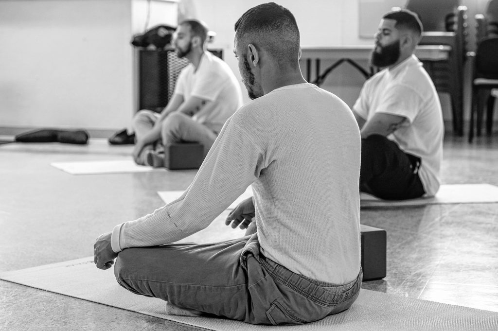 Shawn, left, Gadiel, center, and Michael, inmates at the Hampden County Pre-Release Center in Ludlow, take part in a yoga class in the Cultivating, Honoring and Awakening Men's Potential program, or CHAMP, on Tuesday, April 30, 2019.