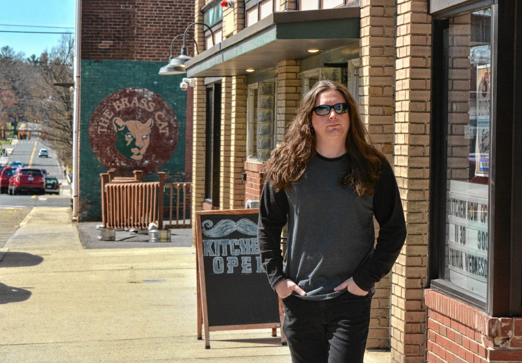 Jonathan Donais, who plays in the bands Anthrax and Shadows Fall, walks along Cottage Street in Easthampton near the Brass Cat and Se7ens, Wednesday, April 17, 2019.