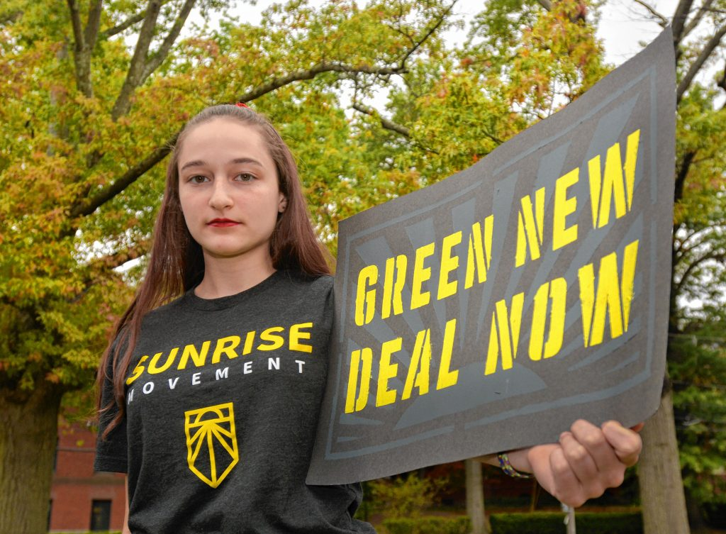 Kala Garrido, a Hampshire Regional High School student who is involved in the climate activist group Sunrise Northampton, holds a sign at Forbes Library, Wednesday, Oct. 16, 2019.