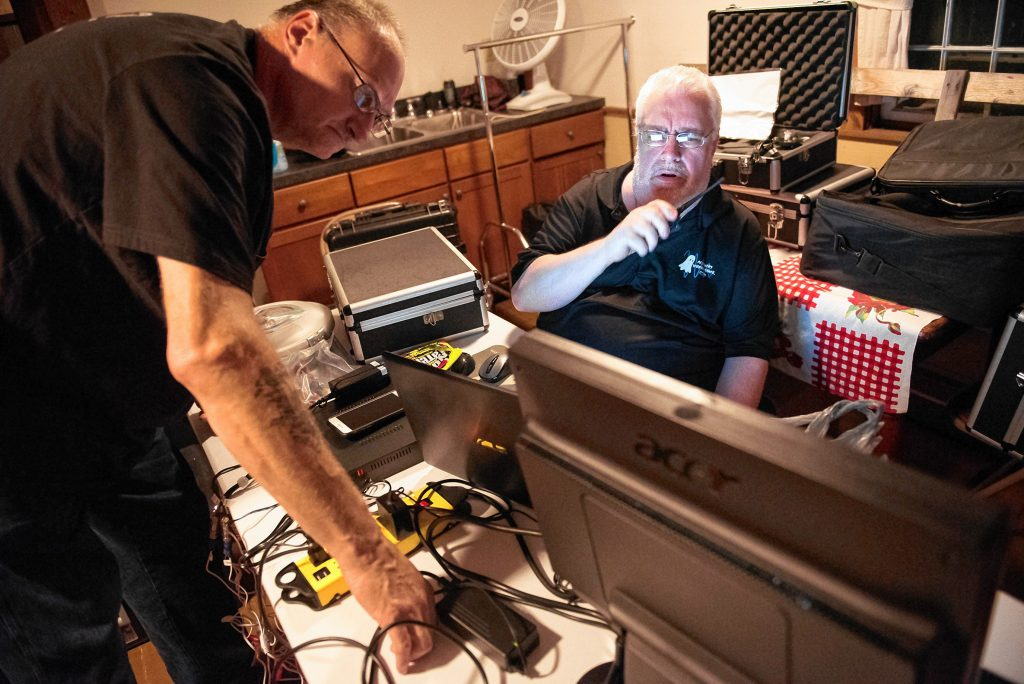 Agawam Paranormal technician/investigator Ed Starkes, left, of Somers, Connecticut, works with lead investigator Rob Goff Sr., seated at the monitoring desk, to solve a connection problem prior to an investigation at the Josiah Day House in West Springfield on Saturday evening, Sept. 14, 2019.