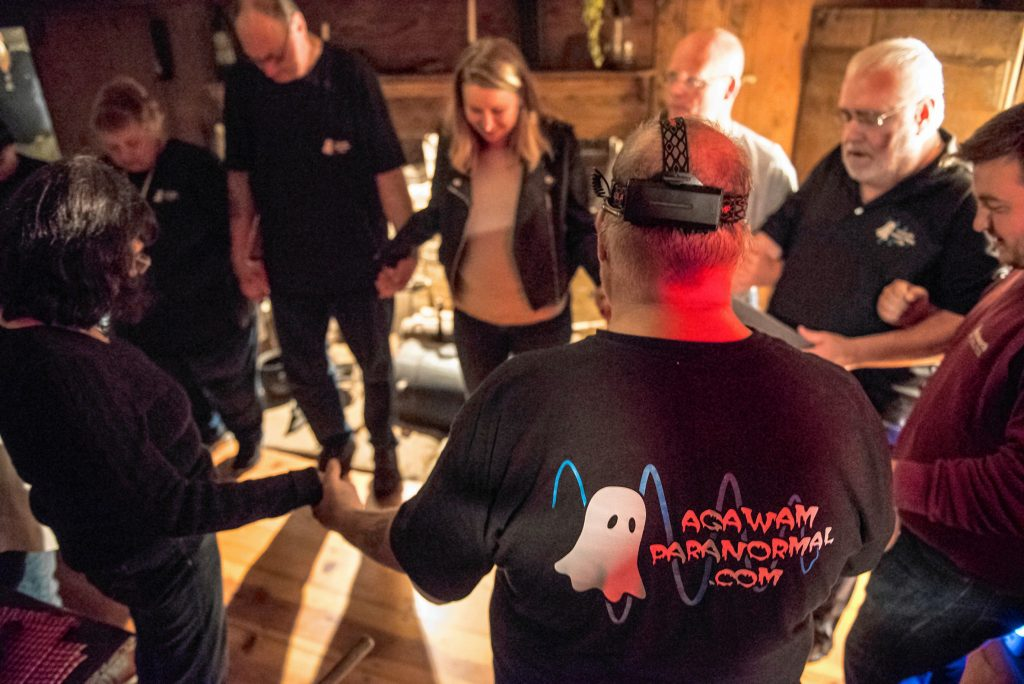Agawam Paranormal director and lead investigator Rob Goff Sr., second from right, leads a prayer with his crew and other visitors in the original kitchen of the Josiah Day House in West Springfield  prior to an investigation there on Saturday evening, Sept. 14, 2019.