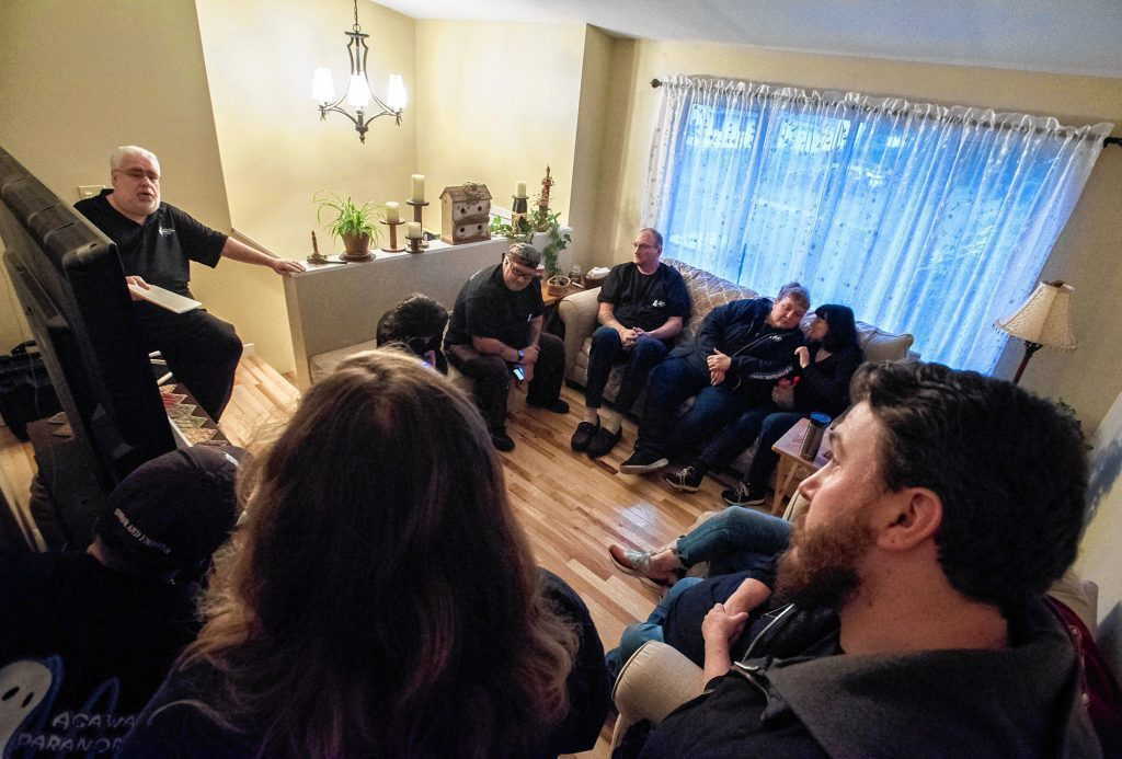 Agawam Paranormal Director Rob Goff Sr., left, conducts a pre-investigation briefing for the crew at his Agawam home on Saturday evening, Sept. 14, 2019, before they head to the Josiah Day House in West Springfield.