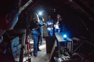Liette Casey, left, with Agawam Paranormal holds two different detection devices as she leads an investigation in the attic of the Josiah Day House in West Springfield on Saturday evening, Sept. 14, 2019.