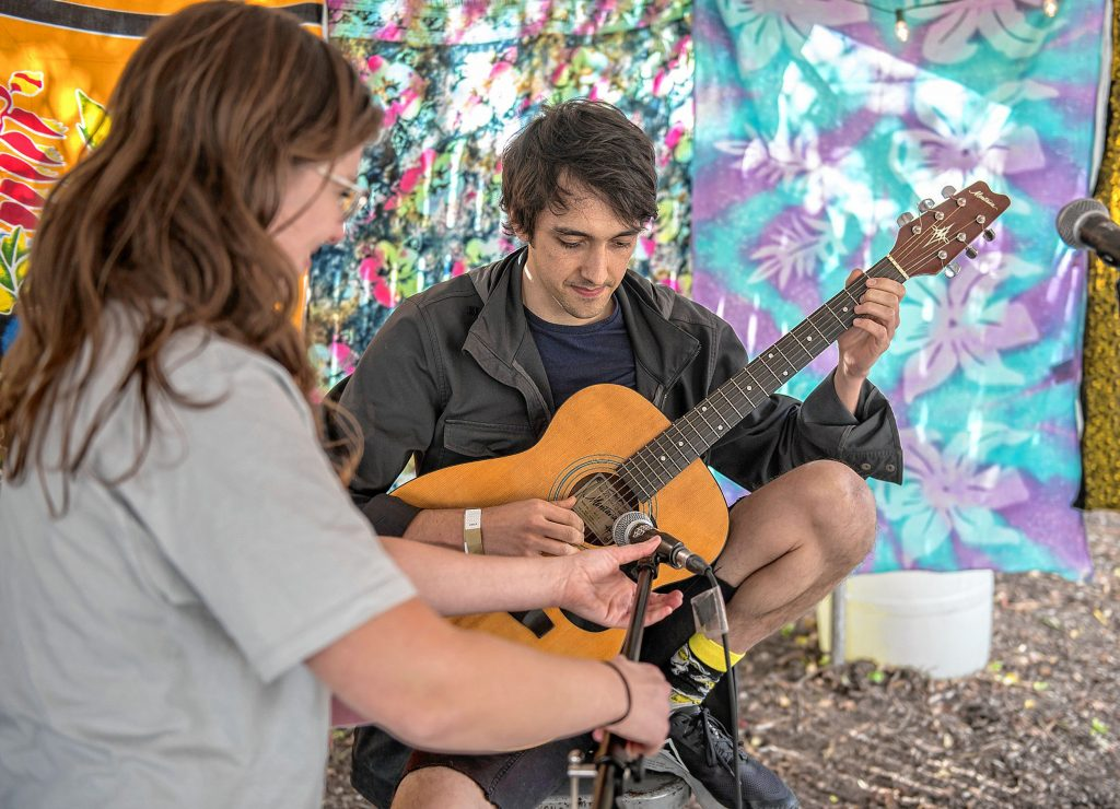 Beth Killian, left, managing the outdoor stage at the Dwellings Arts Festival, helps Matt O'Leary of Holyoke get set up for an early day open mic performance outside the Northampton Center for the Arts on Saturday, Oct. 12, 2019.