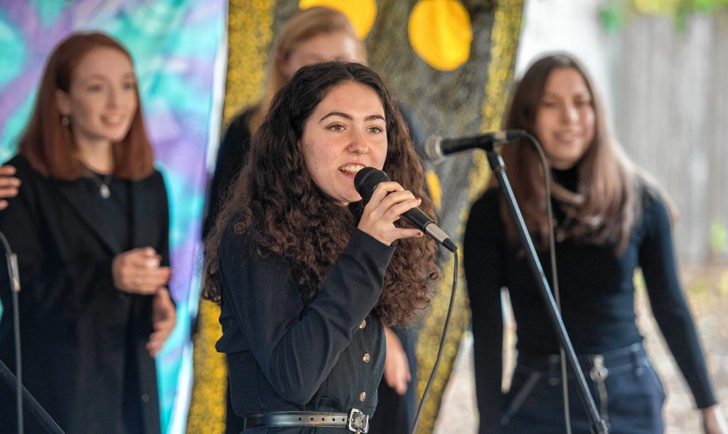 "Bella Donovan and the University of Massachusetts a cappella group S#arp Attitude perform ""God is a Woman,"" by Ariana Grande, during the Dwellings Arts Festival held at the Northampton Center for the Arts on Saturday."