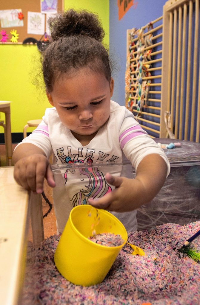 Zoelle Washington, 2, of Holyoke, plays on a sensory table. Though she is not autistic and does not have sensory processing disorders, the activity is suitable for those who do and is offered during the museum's Sensory Sundays. She was with her father, Derek Washington.