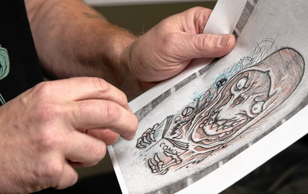Eric Talbot shows Matt Miller what part of Miller's tattoo Talbot plans to work.